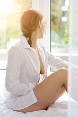 Young attractive woman with open blouse sitting relaxed on bed and looks out of the window