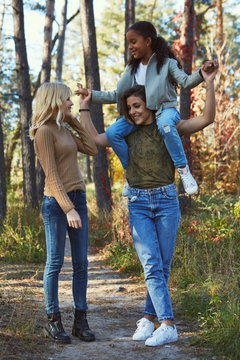 A couple of lesbian ladies with their adopted teenage daughter in the autumn park. The brunette girl holding the kid on her shoulders. The young family standing, holding hands, chatting, smiling.