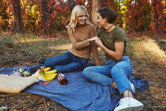 A beautiful couple of lesbian ladies having a picnic in the autumn park. The young women sitting on the ground. Fruit and wine laying on the blanket. The brunette girl holding the blonde girl's hand.