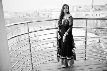 Pretty indian girl in black saree dress posed at balkony.