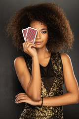 Young afro woman holding playing cards