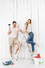 Full length photo of joyous couple man and woman standing on ladder, while painting white wall and making renovation indoor