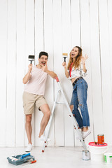 Full length photo of young couple man and woman standing on ladder, while painting white wall and making renovation indoor