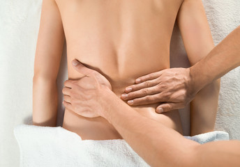 View from above of hands of doctor massaging back of female