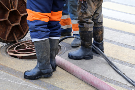 Workers in uniform and wellingtons stand over the open sewer hatch. Concept of repair of sewage, water supply system or underground utilities, cleaning drains, cable laying, water pipe accident