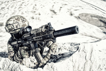Airsoft player in military camouflage uniform, helmet and glasses lying in sand and aiming in optical sight on army service rifle or carbine realistic plastic replica close up desaturated shoot