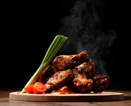 Hot and spicy bbq chicken wings with dip and hot sauce on wooden plate with steam smoke