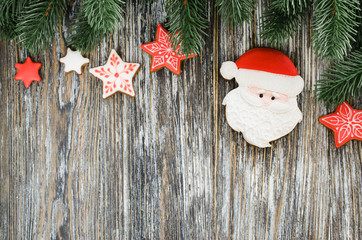 Christmas wooden background with fir tree and gingerbread Santa.