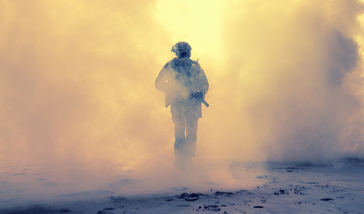 Special operations forces soldier, army ranger or commando in camo uniform, helmet and ballistic glasses walking at battlefield covered with smoke. Airsoft war game player coming through smoke screen