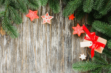 Christmas background with fir tree, gingerbread and gift.