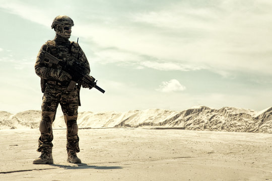 Special operations forces soldier in camouflage combat uniform, helmet and glasses walking in desert with service rifle in hands low angle view. War conflict, military campaign in Middle East region
