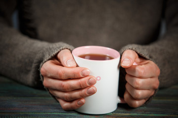Woman holds a cup of hot tea. Cozy morning at home.