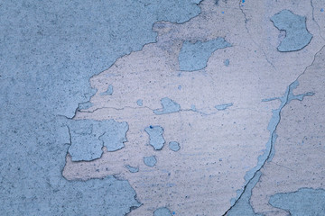 texture of a concrete wall of an old building with peeling blue paint closeup