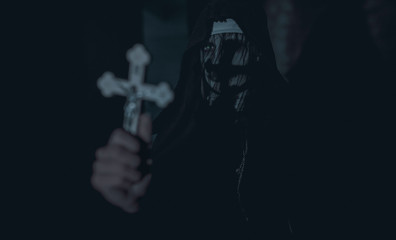 Woman is standing in a darkness with a cross in her hand in an image of a nun possessed by demons.