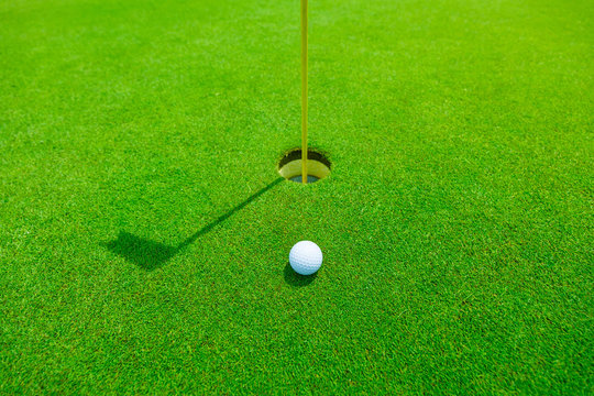golf ball in the green grass close to the hole with the shadow of the flagpole