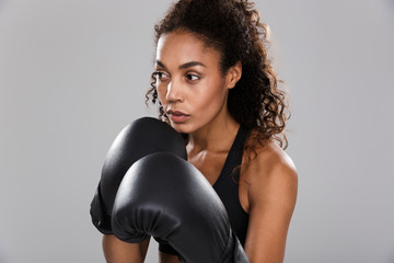 Beautiful african sportswoman isolated over gray