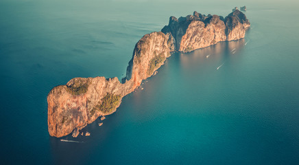 Aerial drone top view on lonely island in Indian ocean. Koh Phi Phi Leh tropical rock island with tourist boats around, Thailand. Travel Background. Nature landscape. Vintage toning filter
