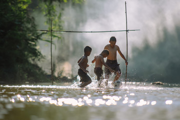 Asian children play soccer in the river,Sport plays an important role in rural and regional Thailand,Sport are the predominantly or exclusively played in rural areas,.