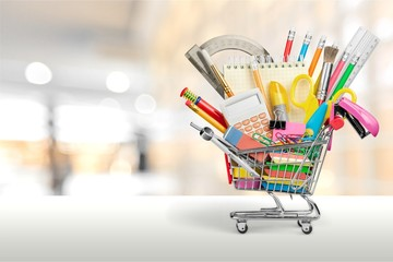 Variety office supplies in little shopping cart on wooden table
