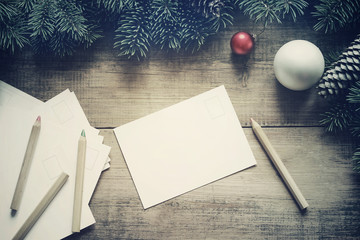 Cards with the place for your text, pencils, glass Christmas spheres and a Christmas fir-tree on a wooden background, top view, toned. Christmas background