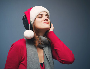 Young girl in Santa's hat and in earphones listens to music with the closed eyes on a blue background. Celebration of new year and Christmas
