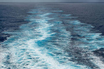 Foam trail in the sea behind the stern of the ship against the horizon