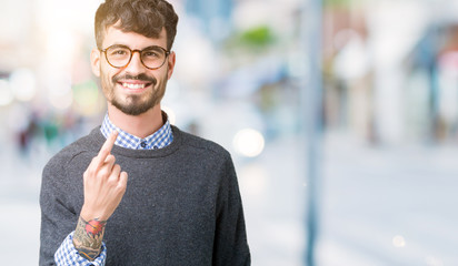 Young handsome smart man wearing glasses over isolated background Beckoning come here gesture with hand inviting happy and smiling