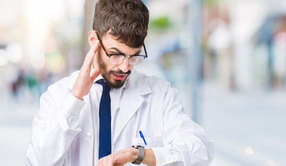 Young professional scientist man wearing white coat over isolated background Looking at the watch time worried, afraid of getting late