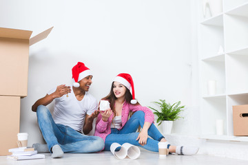 Happy young couple in Santa hats in new house.