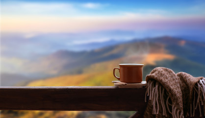 Hot cup of tea or coffee on the wooden railing on the background of the mountains.