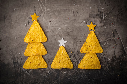 Concept of new year from mexican nachos. Christmas trees made of chips nachos with cheese on a dark background. Copy space