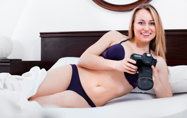 Foto op Canvas Akt Young woman in underwear in bed and taking pictures with camera