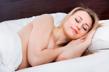 Foto op Canvas Akt Naked woman sleeping in the bed covered with a blanket
