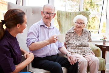 Male And Female Residents Sitting In Chair And Talking With Carer In Retirement Home