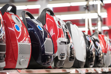 Row of vacuum cleaners in appliance store