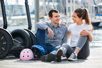 Positive tourists couple relaxing near segways