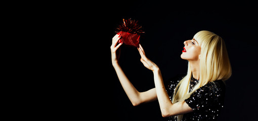 Portrait of a beautiful blonde woman holding a red gift, isolated on black studio background