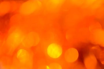 Bokeh. Holiday background. Christmas lights. Glitter. Defocused sparkles. New Year backdrop. Festive wallpaper. Blinks. Carnival. Bokeh retro style photo. Orange.