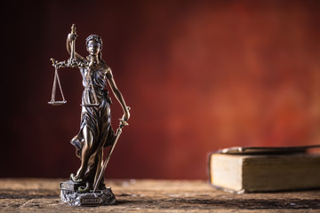 Lady Justicia holding sword and scale bronze figurine with book on wooden table