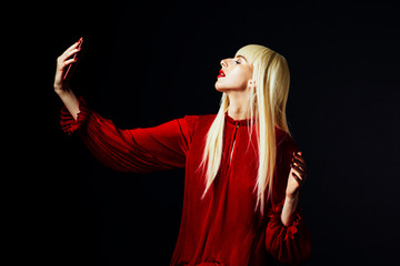 Portrait of a beautiful blonde woman in red holding a smartphone taking a selfie ,isolated on black studio background