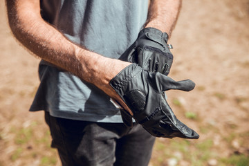Crop man putting on gloves