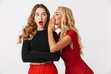 Emotional young two girls friends gossiping isolated over white wall dressed in black and red clothes.