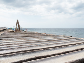 Production of sea salt in the Bali,Indonesia. Salt crystallizes out of the ground in salt farm, filled with natural salt from the sea.