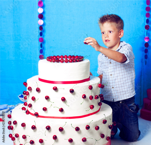 7 Year Old Boy Decorates Huge White Cake By Red Cherry Blue Background In Studio