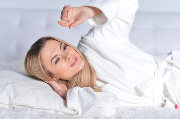 Beautiful young woman lying on soft  bed