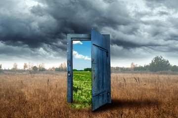 Creative background. Old wooden door, blue color, in the box. Transition to a different climate....