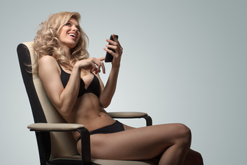 Smiling Blonde wearing black underwear sitting on a chair with cellphone receiving a message