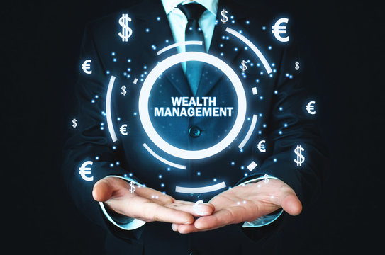Businessman holding Wealth Management word with currency symbols.