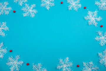 Creative Christmas layout. Snowflakes on blue background whit copy space. Border arrangement. Flat lay top view.