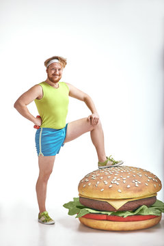 Red haired, bearded, plump man put his leg to a huge sandwich